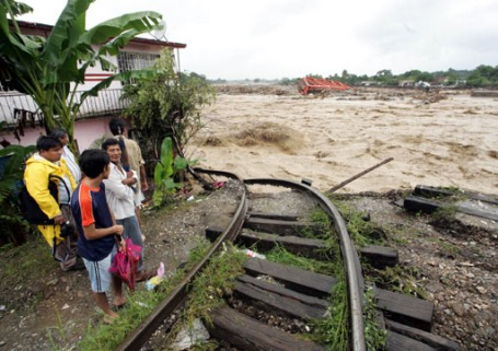 Residents look at the destruction of a train line and of a bridge caused by heavy rains from Hurricane Stan in the town of Tapachula in the southern Mexican state of Chiapas Mexico, October 6, 2005. Raging flood waters cut off large areas of Central America and southern Mexico on Thursday, hurting efforts to rescue victims of mudslides that have killed at least 164 people in the wake Hurricane Stan. REUTERS/Henry Romero